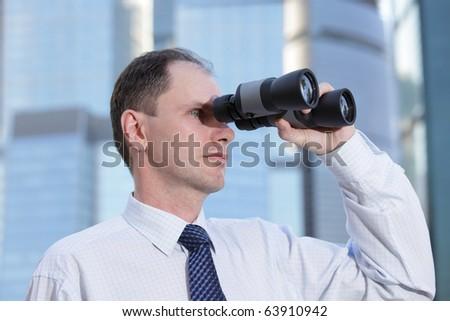 Businessman with binoculars against modern office buildings - stock photo