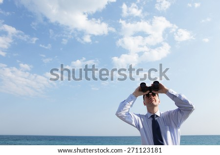 Businessman with binoculars looking upward against a sea and skyscape  - stock photo