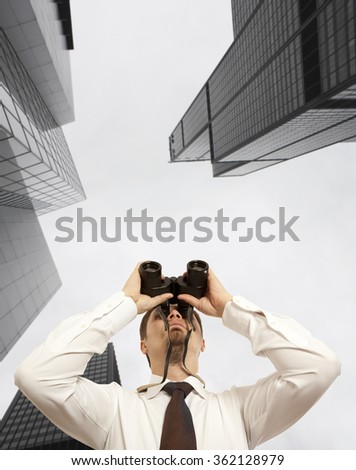 Businessman with binoculars. Over city background - stock photo