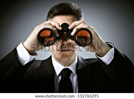 Businessman with binoculars. Over gray background. - stock photo