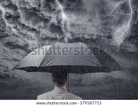 Businessman with black business umbrella protecting himself from the storm concept for insurance, financial protection from recession or economic depression - stock photo