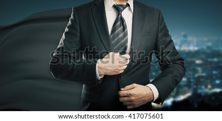 Businessman with black superhero cape on night city background