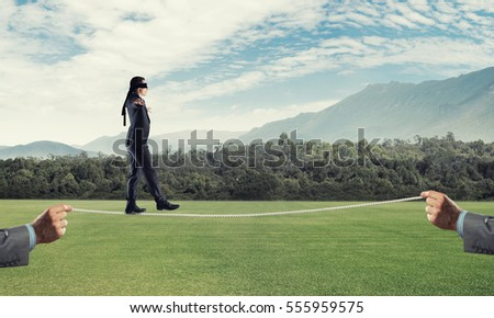 Businessman with blindfolder on eyes walking on rope over natural background