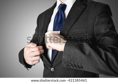 Businessman with blue tie putting fifty euro notes into a pocket in his suit.