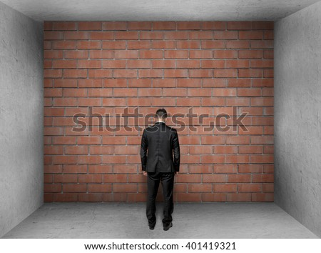 Businessman with bowed head stands front of a brick wall in interior.