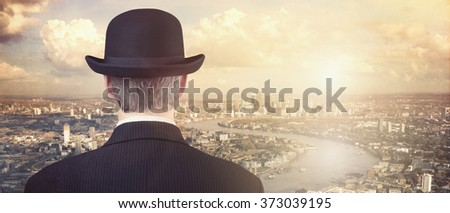Businessman with bowler hat looking at financial city skyline concept for finance, investment, career and opportunity - stock photo