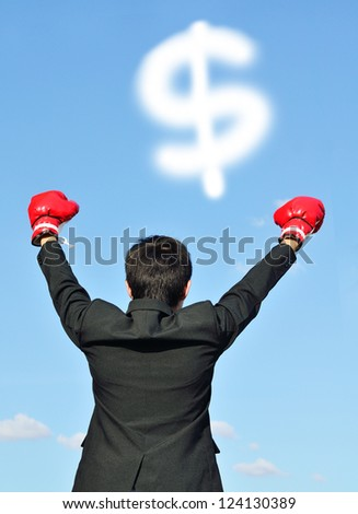 businessman with boxing glove and dollar sign over blue sky