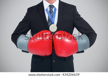 Businessman with boxing gloves against grey background