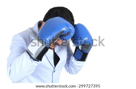 Businessman with boxing gloves guarding his face - stock photo