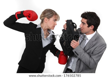 Businessman with boxing gloves hitting man - stock photo