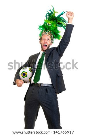 Businessman with brazilian soccer ball and Carnaval head dress isolated in white - stock photo