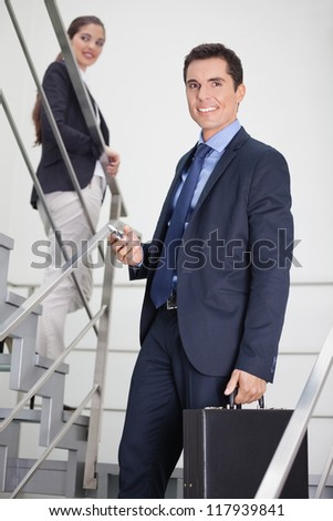 Businessman with briefacse and woman walking down a stairway - stock photo
