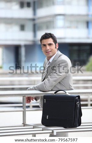 Businessman with briefcase in an urban environment - stock photo