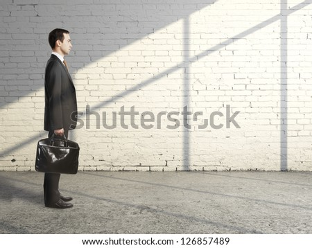businessman with briefcase in brick loft - stock photo