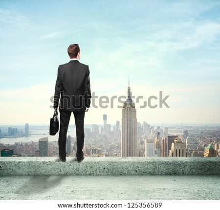 Businessman with briefcase looking at city standing on roof - stock photo