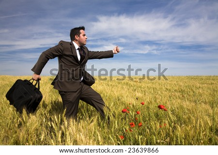 Businessman with briefcase running in a field - stock photo