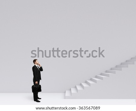 businessman with briefcase standing near ladder - stock photo