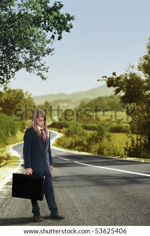 Businessman with briefcase standing on road