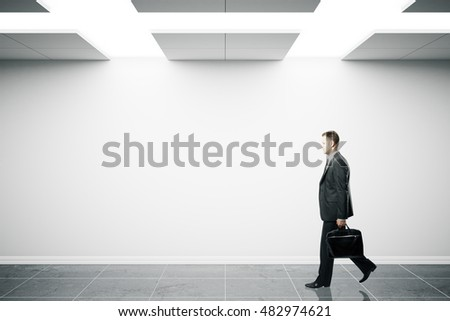 Businessman with briefcase walking in minimalistic interior with blank wall. Mock up, 3D Rendering