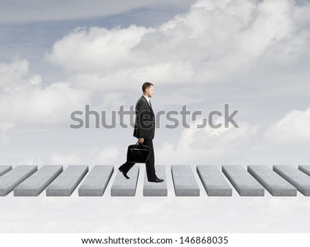 businessman with briefcase walking on sky - stock photo