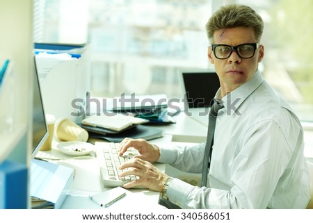 Businessman with bruised face typing at workplace - stock photo