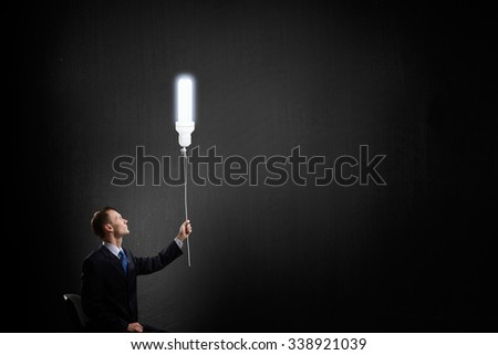Businessman with bulb on rope representing bright idea - stock photo