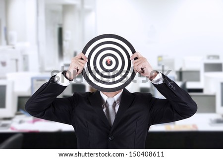 Businessman with bull's eye head dartboard in the office - stock photo