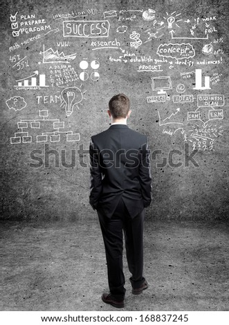 businessman with business concept on wall - stock photo
