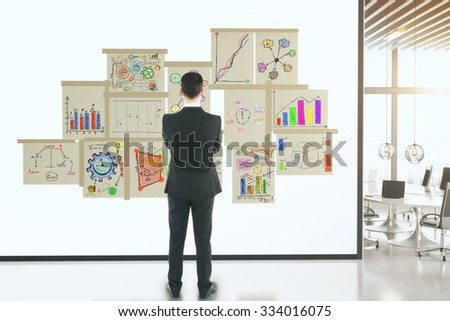 Businessman with business concept scheme on posters on white wall - stock photo