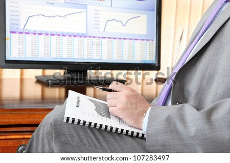 Businessman with Business plan.  Male hand with pen  on the  Business plan in front of computer screen with financial data and charts