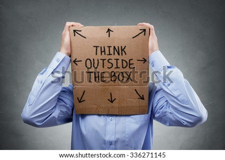 Businessman with cardboard box on his head saying think outside the box concept for brainstorming, creativity, innovation, strategy or individuality - stock photo