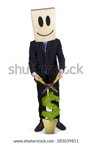 Businessman with cardboard head and smiley icon, using scissors to cut money tree - stock photo