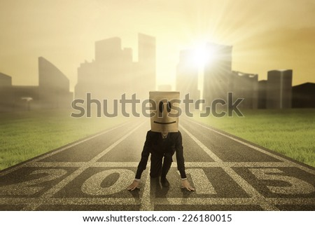 Businessman with cardboard head kneeling on track competition and ready to compete in future 2015 - stock photo