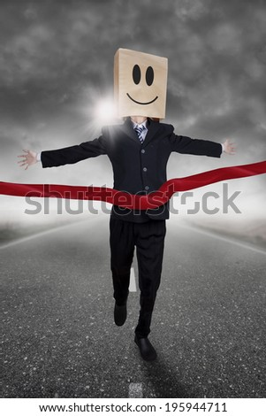 Businessman with cardboard head winning a race competition - stock photo