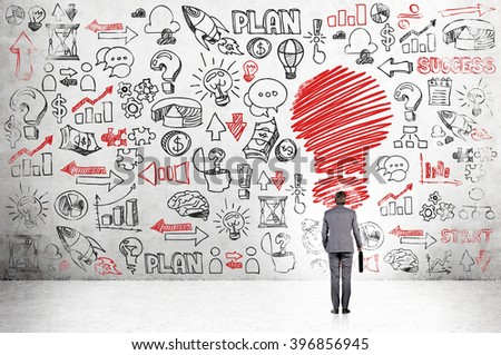 Businessman with case standing in front of concrete wall with many business icons, red bulb in front. Back view. Concept of having new idea. - stock photo