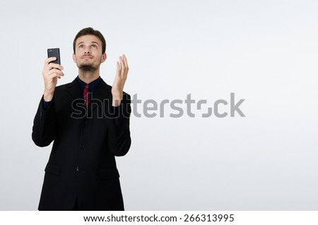 Businessman with cell phone and hands up