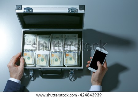 Businessman with cellphone and case full of money