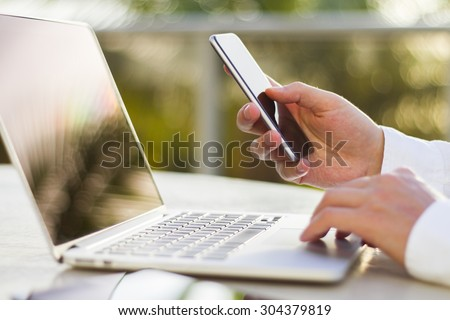 businessman with cellphone and laptop at morning - stock photo
