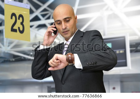 Businessman with cellphone in the airport - stock photo