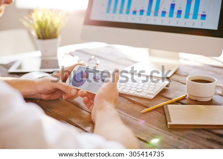 Businessman with cellphone looking at diagram with financial data - stock photo