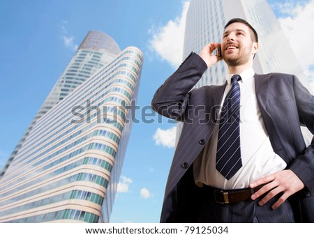 Businessman with cellphone on a background of skyscrapers - stock photo