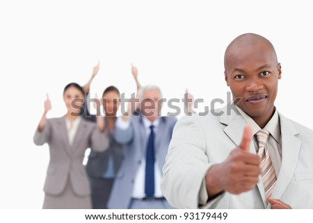 Businessman with cheering team behind him giving approval against a white background - stock photo