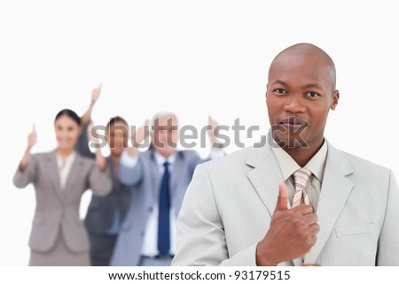 Businessman with cheering team behind him giving thumb up against a white background - stock photo