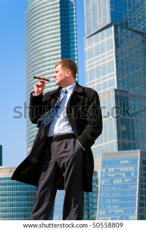 Businessman with cigar near skyscrapers