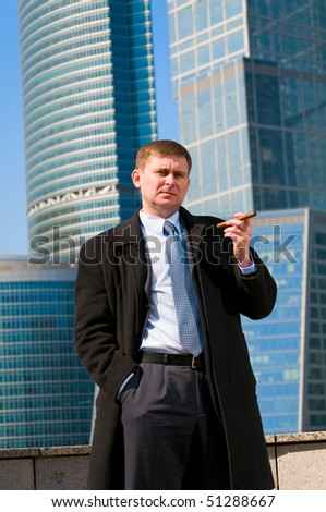 Businessman with cigar near skyscrapers - stock photo