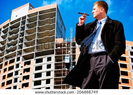 Businessman with cigar on industrial background