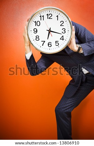 Businessman with clock on head, studio shot.