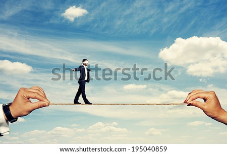 businessman with closed eyes balancing on the rope