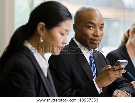 Businessman with co-workers holding phone in conference room - stock photo