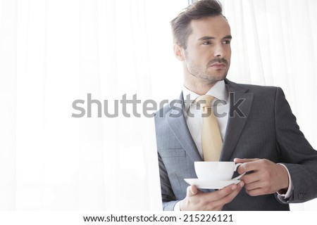 Businessman with coffee cup looking away in office - stock photo